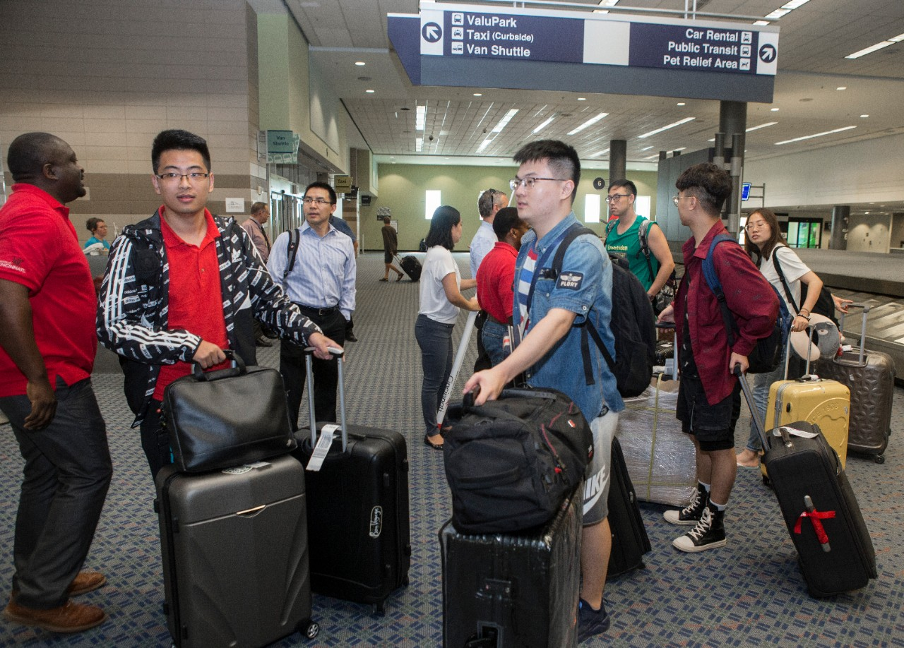 Students gather suitcases in an airport terminal.