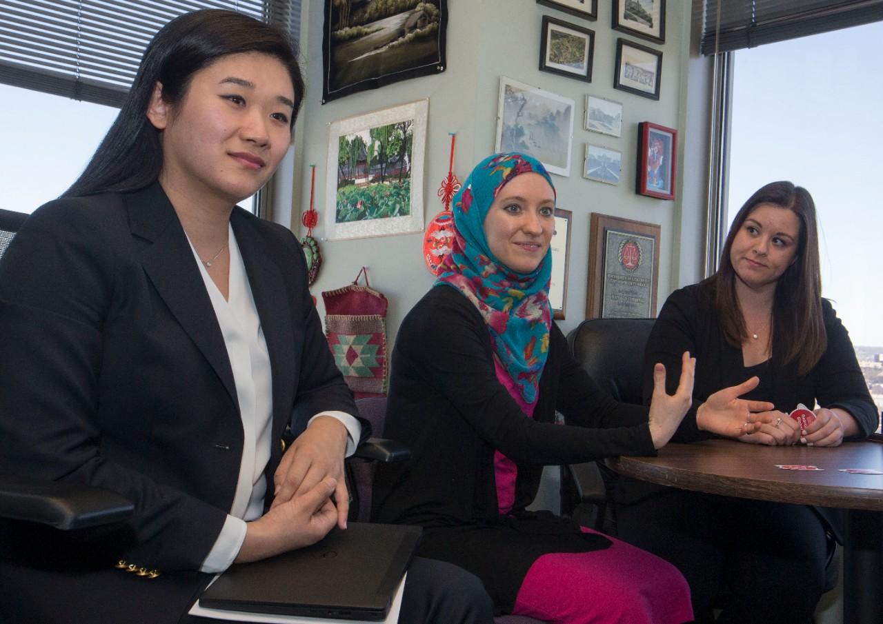 UC International staff talk around a table.
