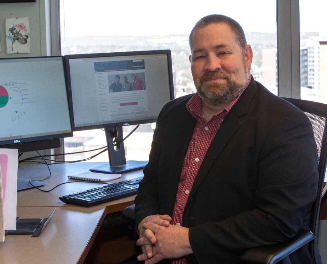 Ronald Cushing sits at his desk.