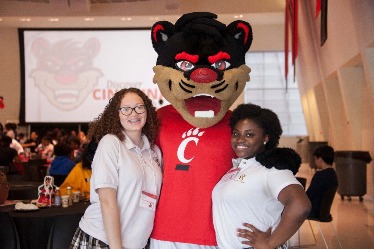 The bearcat mascot stands with his arms around two black female students