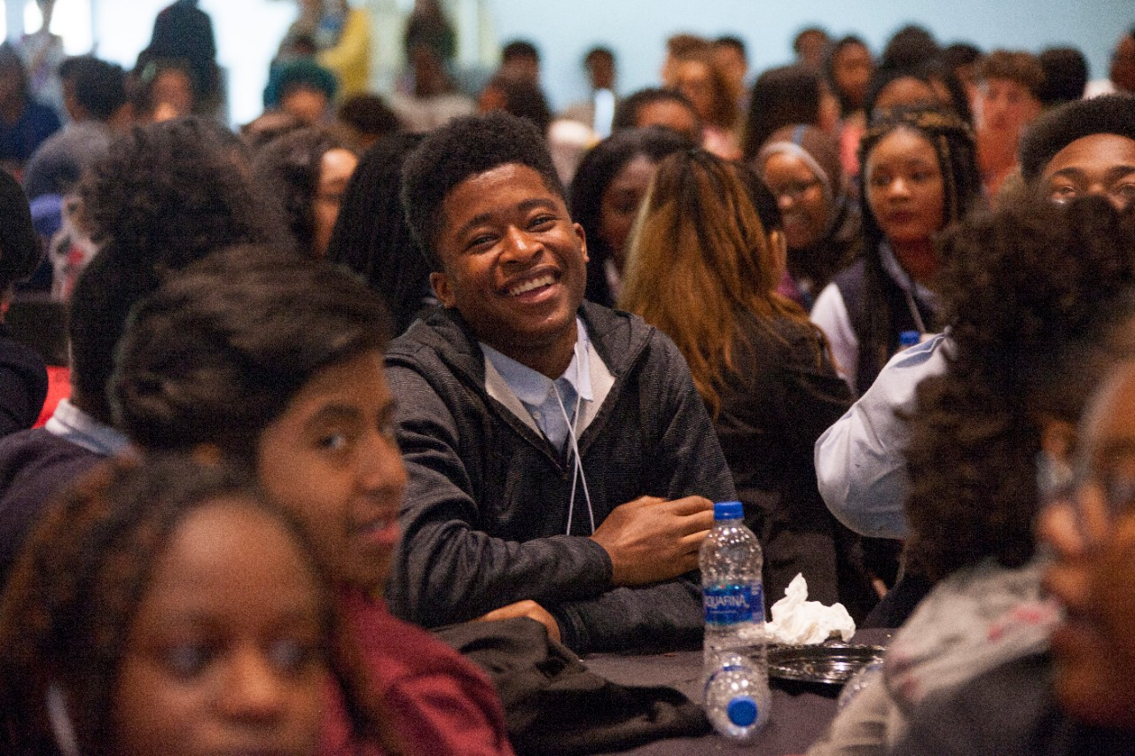 A student sitting in a crowded room laughs