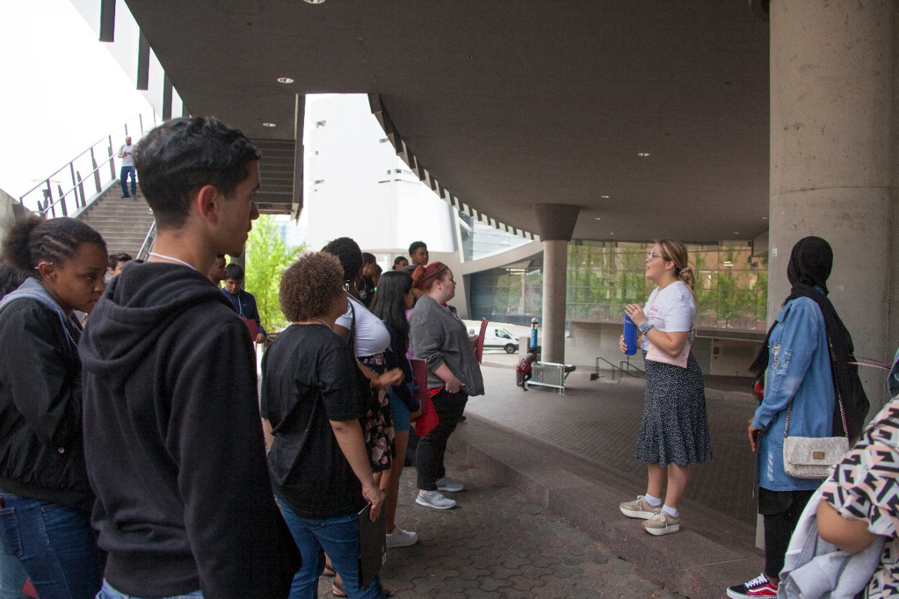 A college student leads a group of high school students on a tour of campus