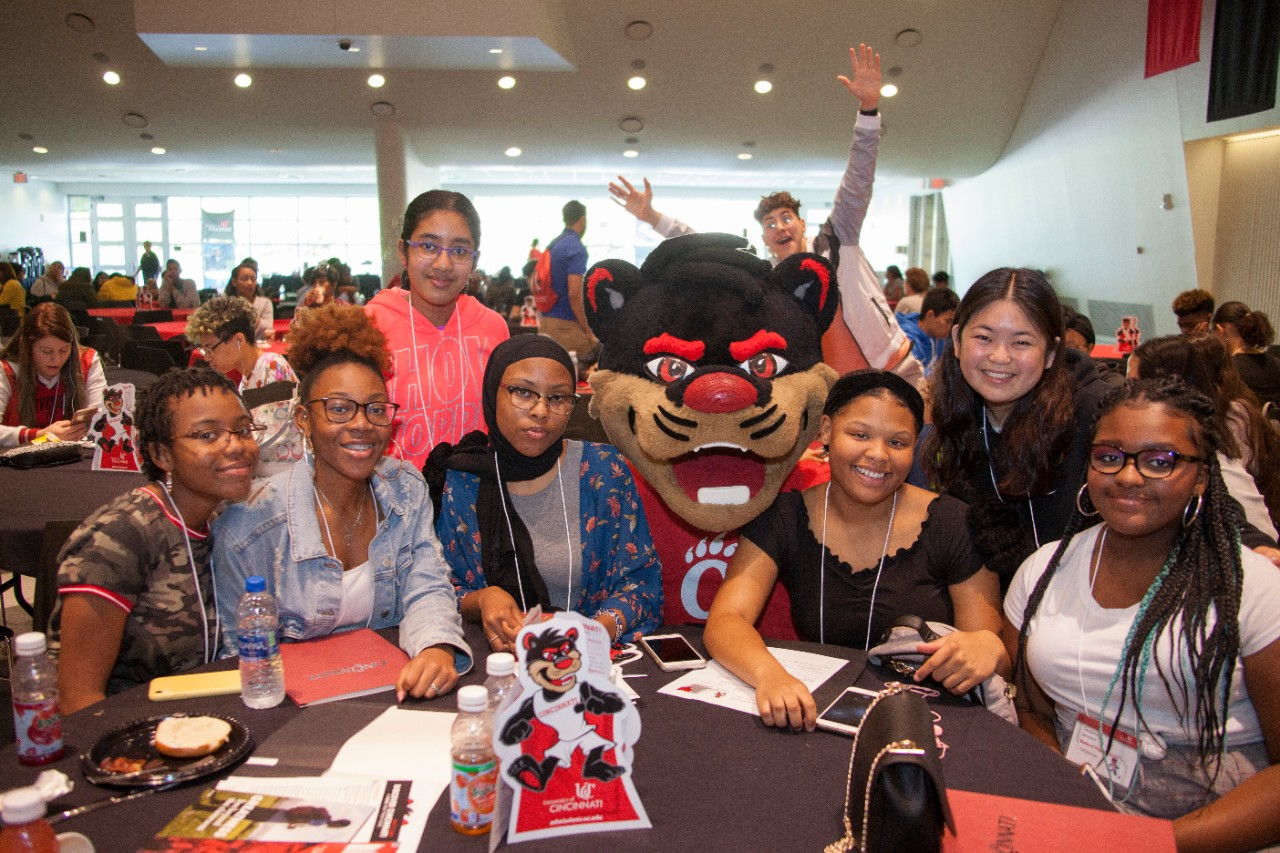 a group pf students sit at a table with the Bearcats mascot