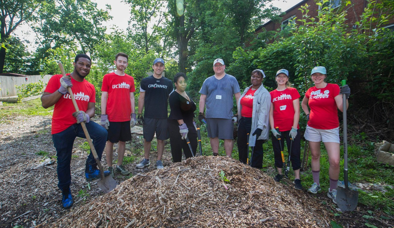 Eight people stand around a giant mound of mulch in a garden.