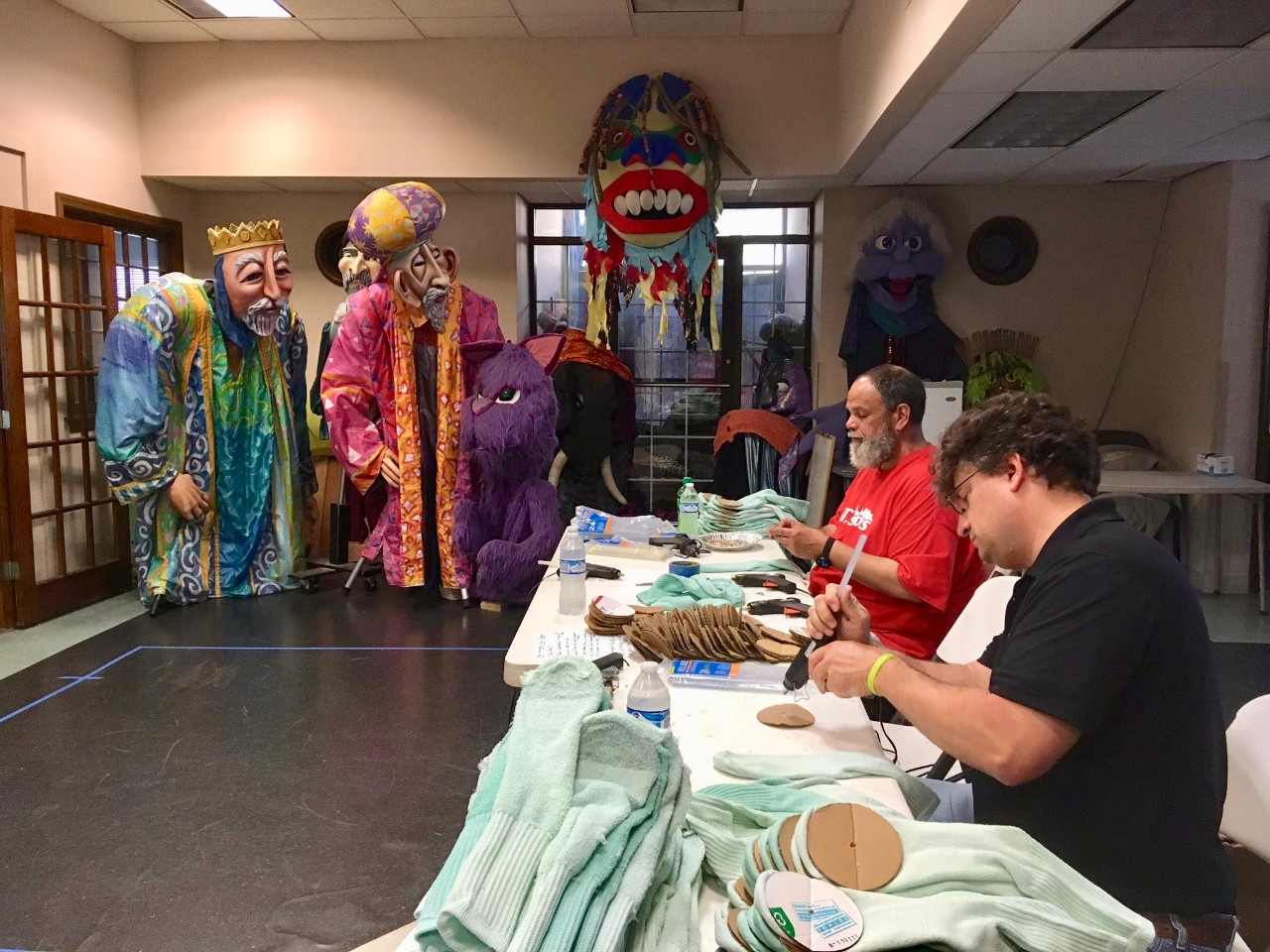 Two people sit at a table sewing costumes for large puppets standing in the background.