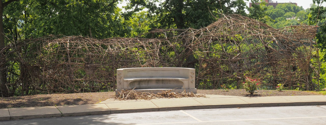 A tunnel-like structure of sticks stands behind a concrete bench outside