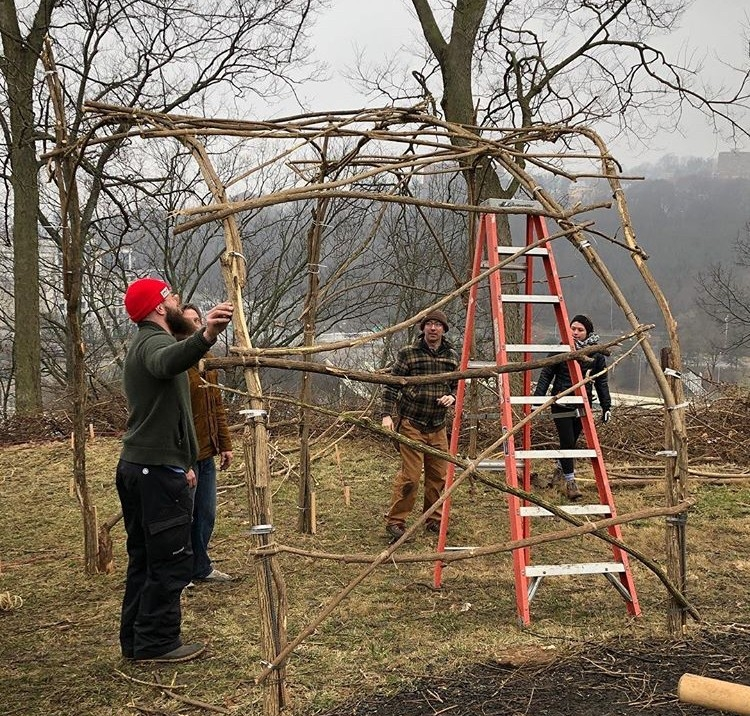 People constructing the temple with honeysuckle branches