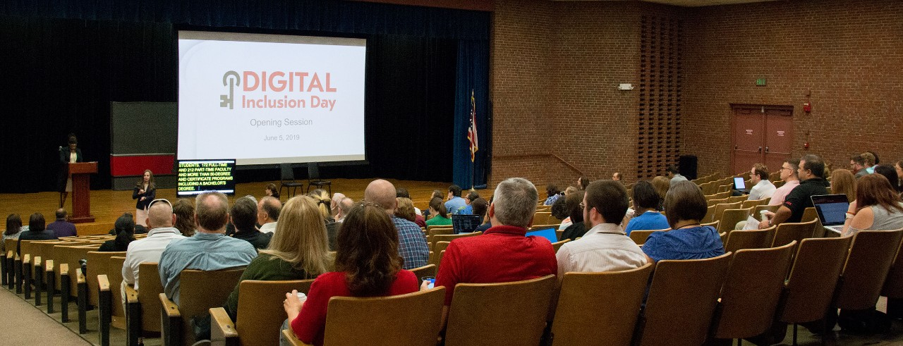"""Wide shot of an auditorium with a large audience; a speaker speaks next to a CART writer along with a screen with the title """"Digital Inclusion Day"""""""