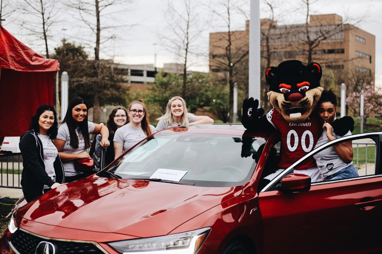 Students and the Bearcat gather around a car