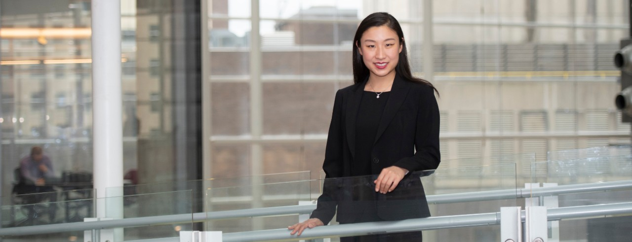 Dermatology resident Yang Yu, MD, standing on a bridge in the CARE/Crawley Building on the UC medical campus