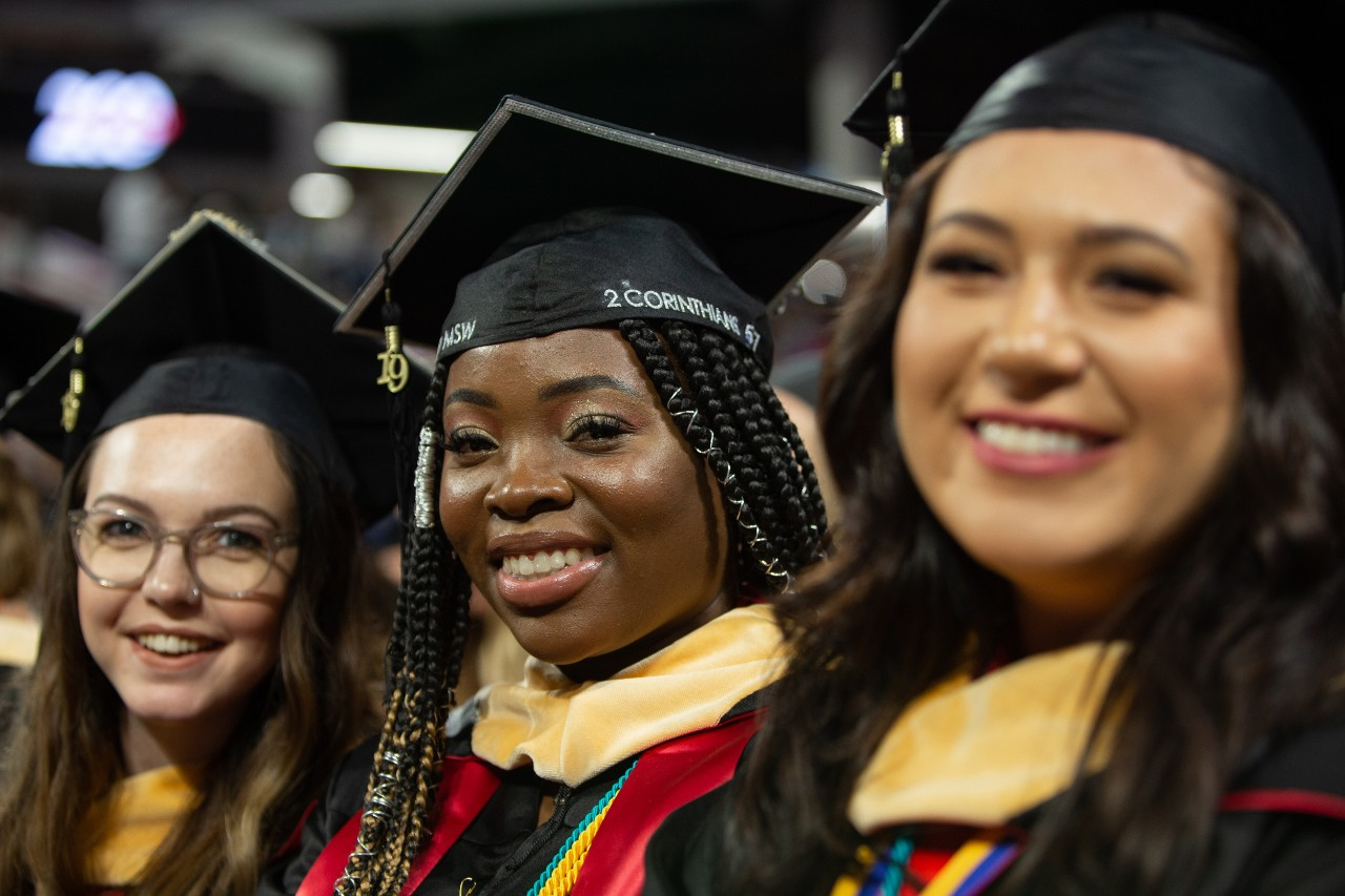 Three students in caps and gowns smile during commencement.