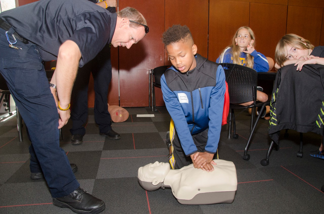 An elementary-aged boy learning CPR with assistance