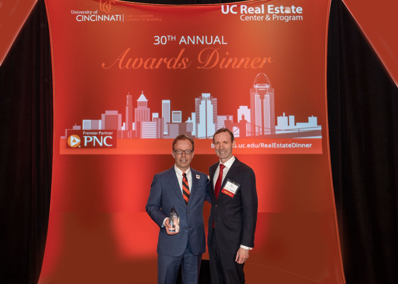 Two men in suits and red ties stand and smile in front of background for real estate center