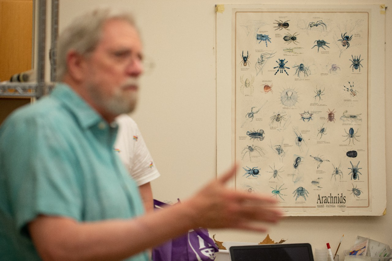 George Uetz stands out of focus in the foreground of his lab while a poster in the background shows dozens of different species of spiders.