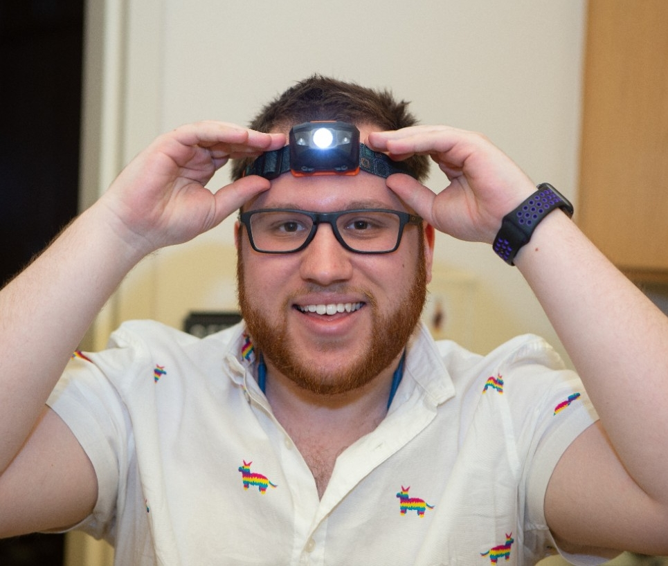 A student smiles while turning on a headlamp in a biology lab.