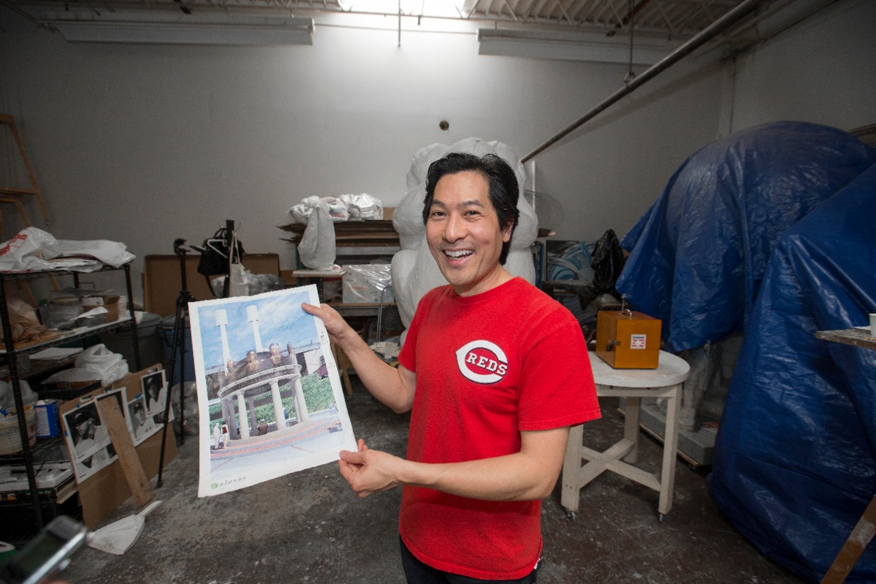 A man in a red T-shirt holding up a picture of an open-sided, domed structure