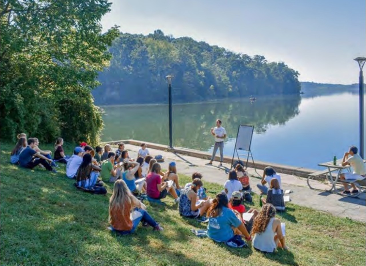 UC students sit on the edge of a pond as they participate in a Sustainability Summit.