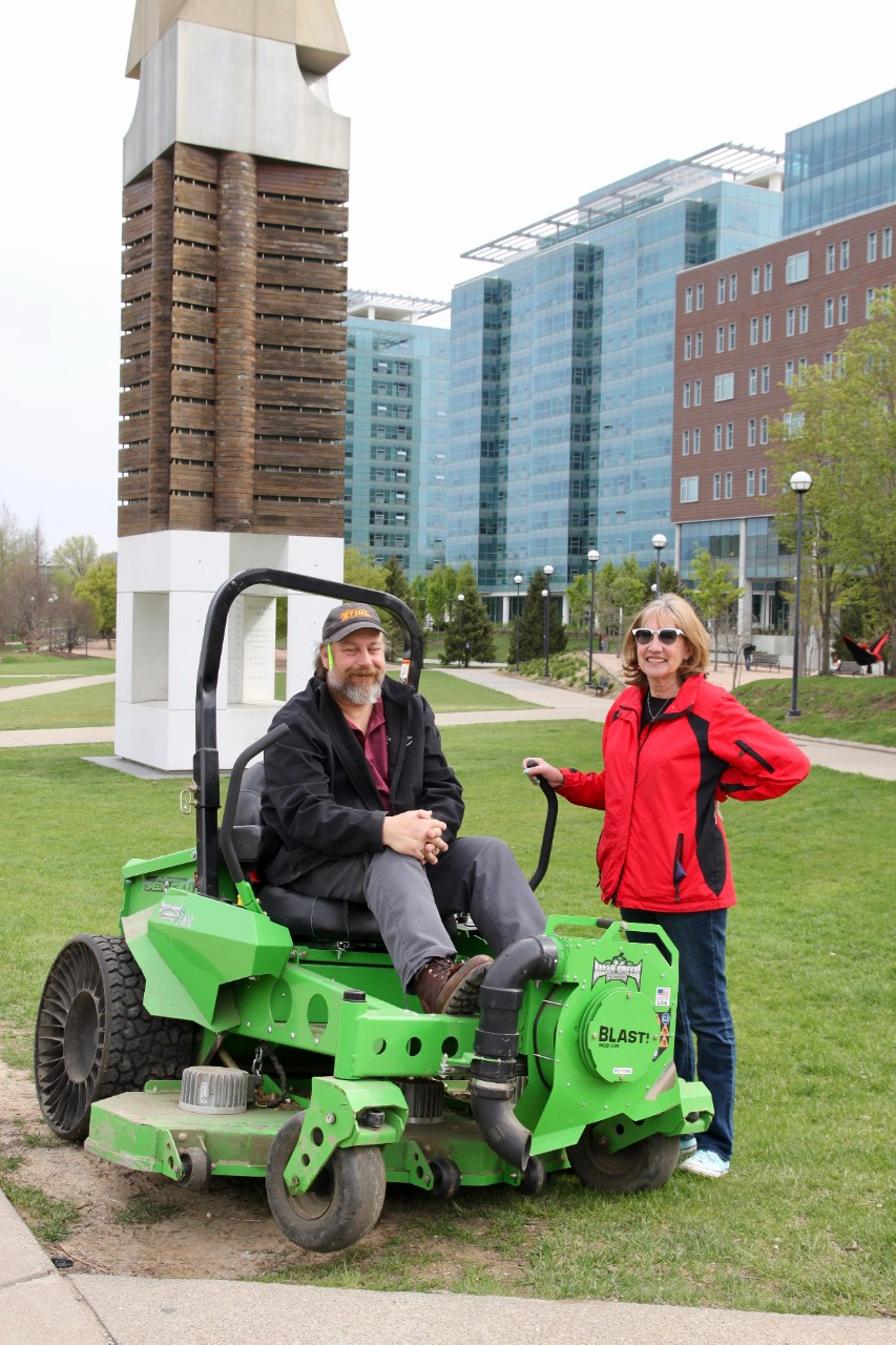 A man sits on UC's solar- and battery-powered lawn mower with a woman standing beside it.