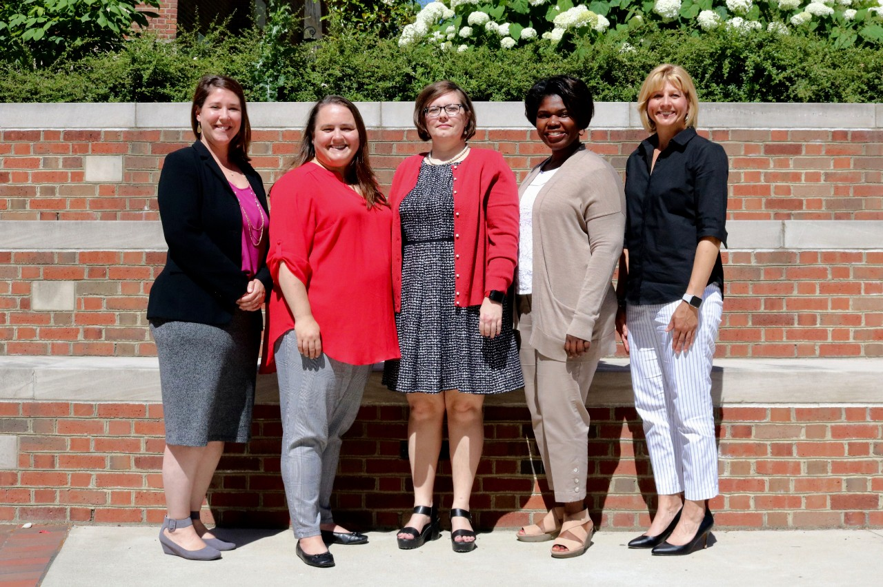 Five staff senate women stand together in UC's campus.