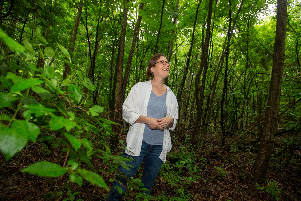 Theresa Culley stands in a forest full of green vegetation.