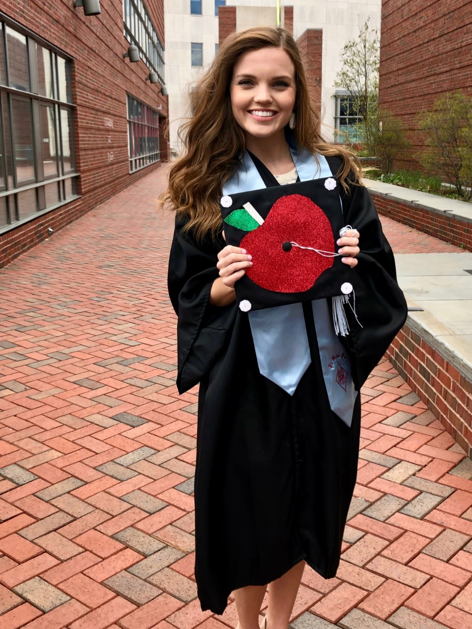 Amanda Bright, UC CECH grad, holds her graduation cap to show the teacher's apple design she created on the top.
