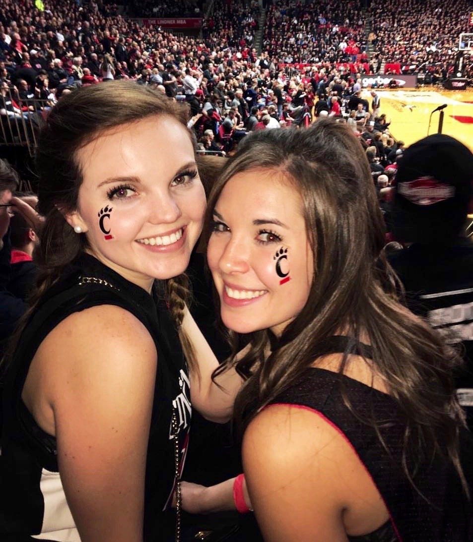 Amanda Bright, UC CECH student, poses with a woman at a UC basketball game.