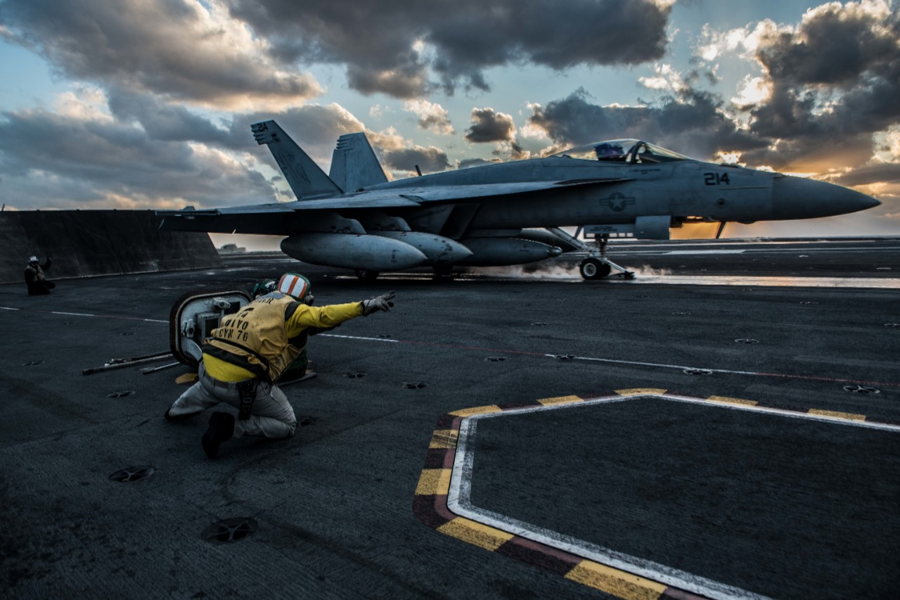 An F-18E Super Hornet takes off from the deck of the USS Ronald Reagan with the setting sun behind it.