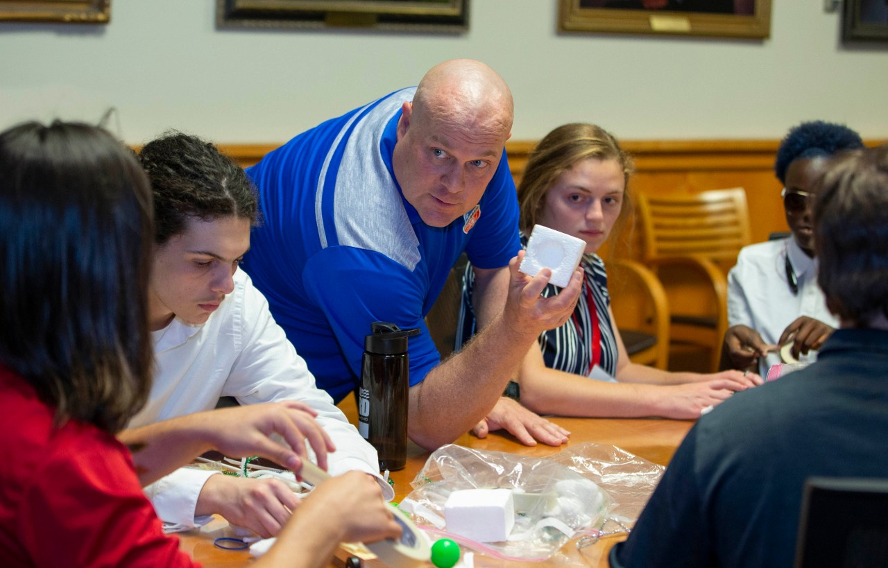 UC's Don Wittrock leans over a table of students as he holds a styrofoam cube.