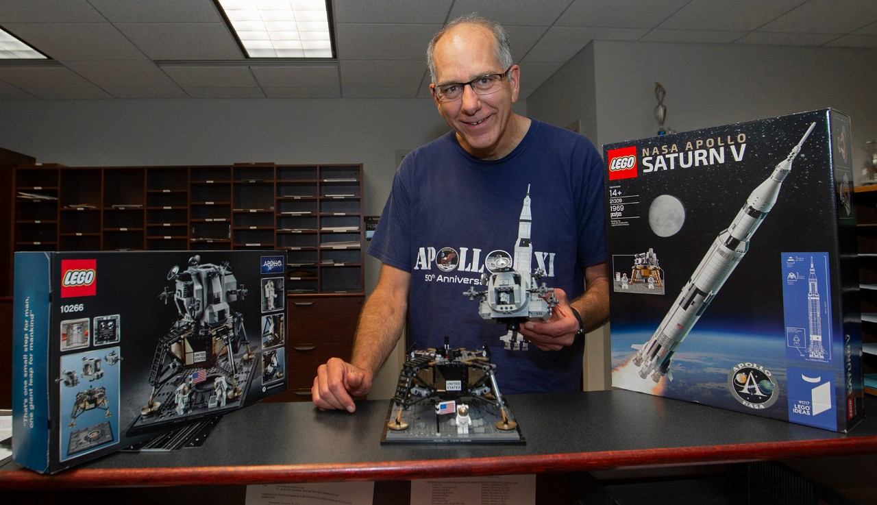 Mark Turner wears an Apollo 11 T-shirt and plays with a Lego lunar capsule.