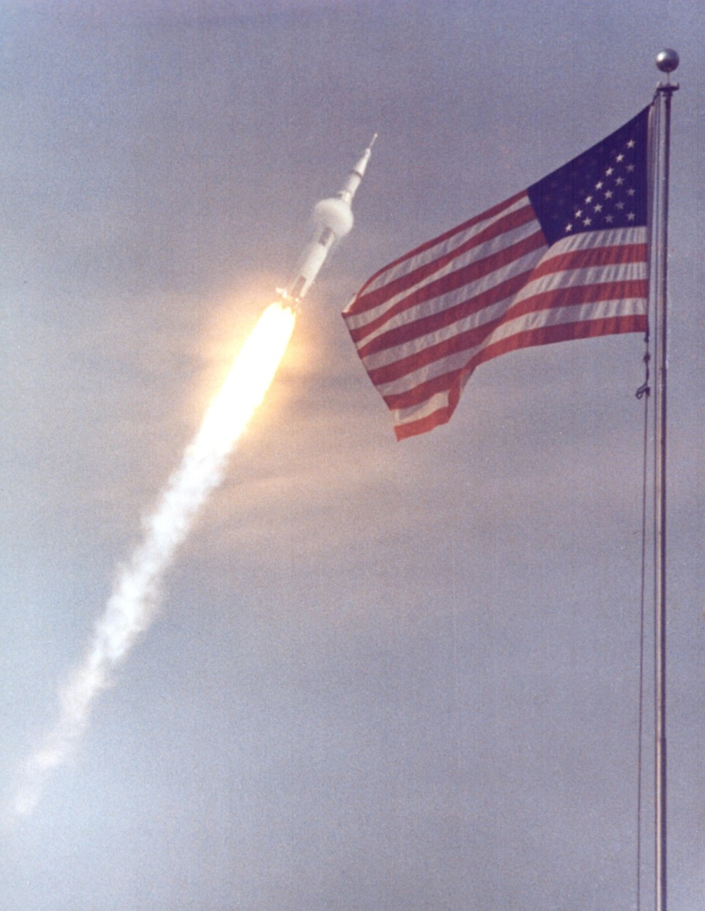 The Apollo 11 rocket blasts off with the American flag waving in the foreground.