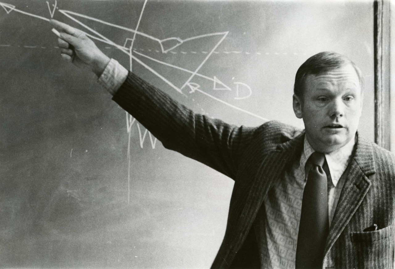 Neil Armstrong stands at a chalkboard.