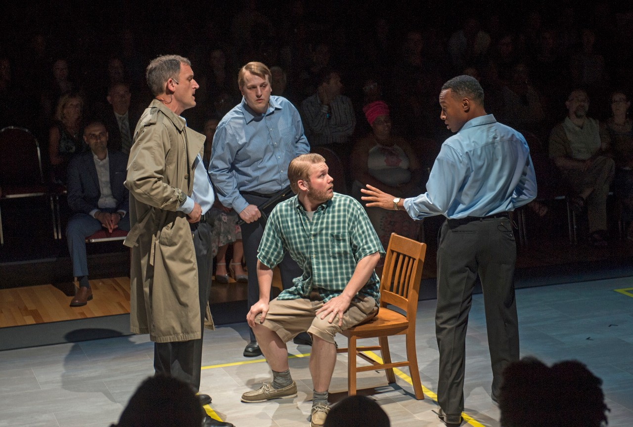 Stage scene of man in chair being interrogated by three other men
