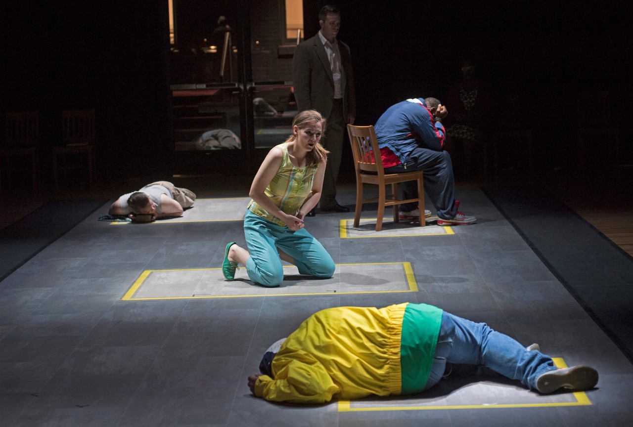 Actors kneel and lay down on stage as part of opera