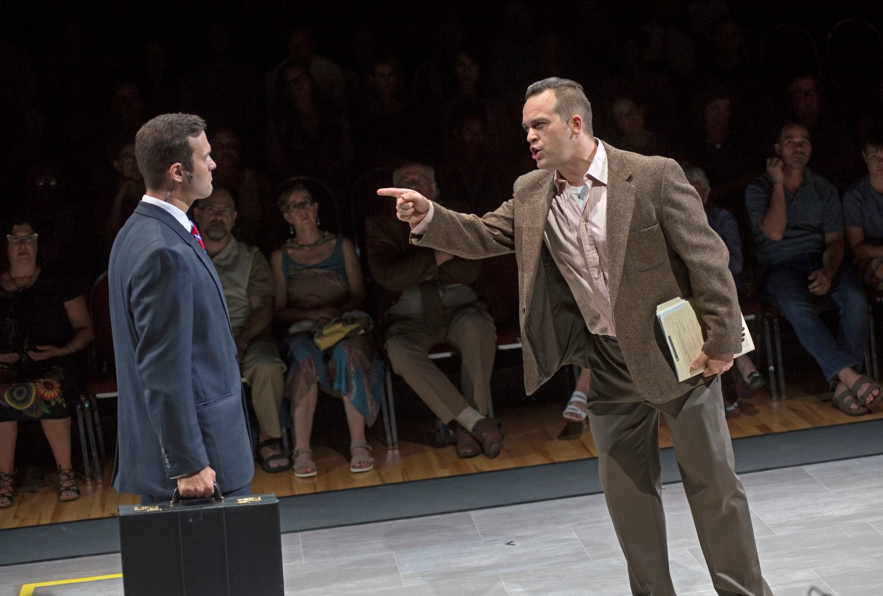 Stage scene of a man pointing in the face of another man carrying a briefcase