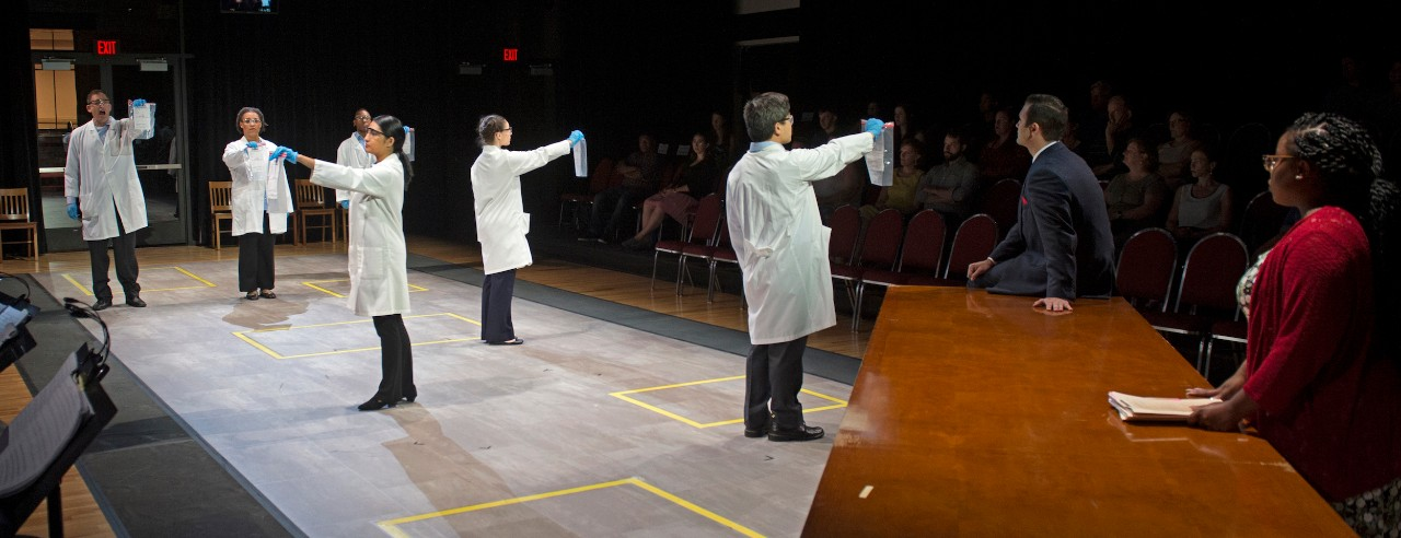 Scene from Blind Injustice opera shows actors in lab coats holding test kits