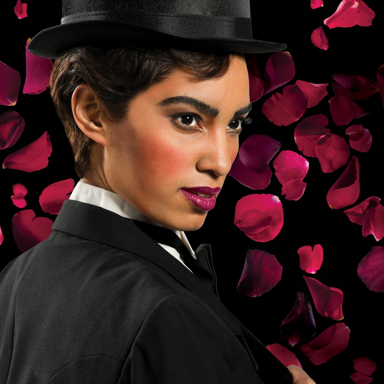 A woman wears a suit and top hat in a promotional image for the opera 'Partenope.' Photo by Mark Lyons.