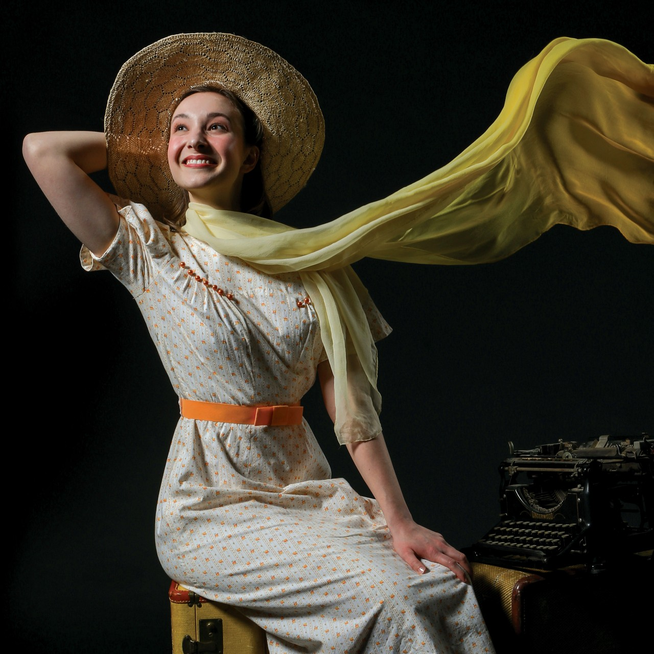 A woman staring hopefully into the distance while sitting in front of a typewriter in a promotional image for the musical 'Bright Star.' Photo by Mark Lyons.