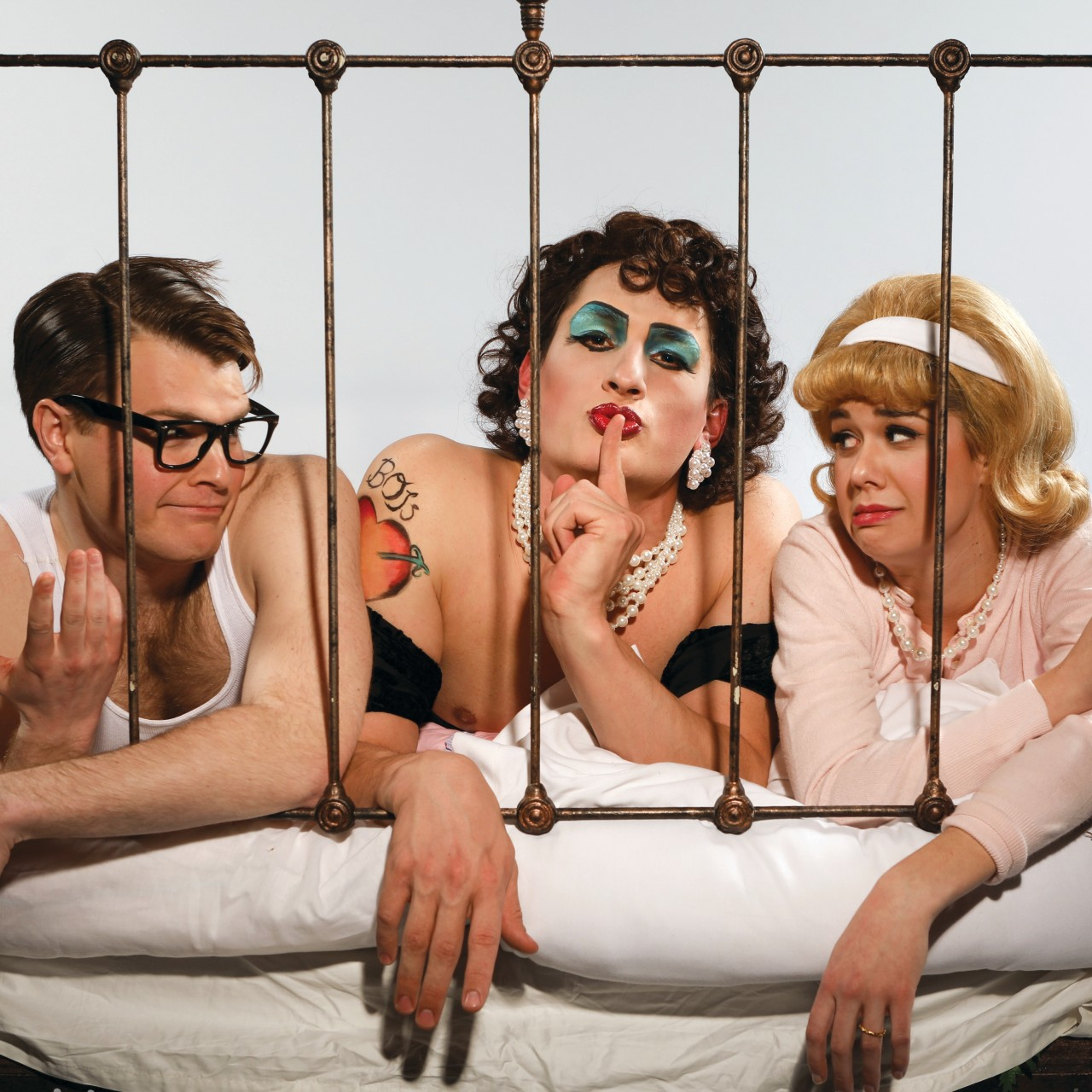 Two men and a woman posing on a bed in a promotional image for the rock musial 'Rocky Horror Show.' Photo by Mark Lyons.