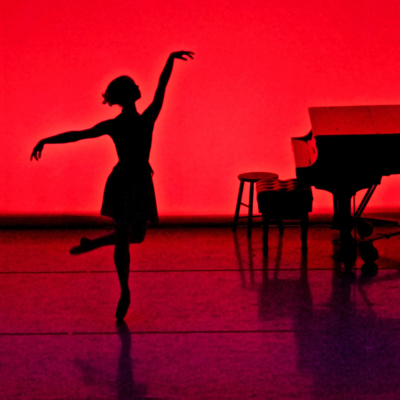 A single female ballet dancer is pictured in silhouette next to a piano against a red backdrop in a promotional image for the dance performance 'The Art of Motion.' Photo by Will Brenner.