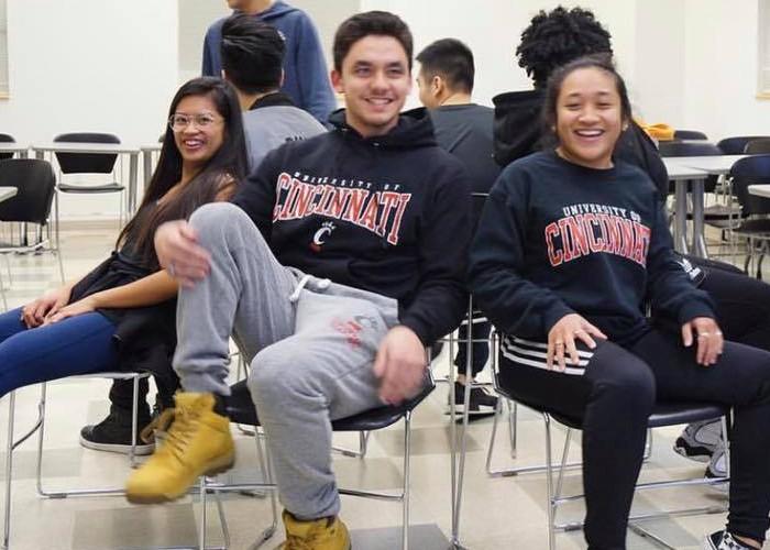 3 UC students sitting inside