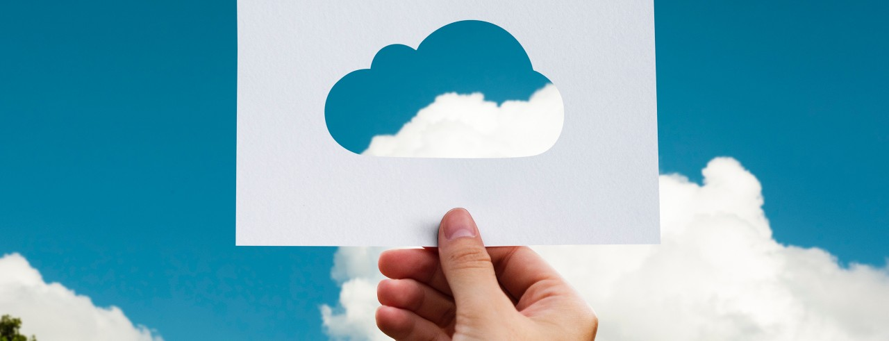 Hand holding a card with cloud cutout; fluffy white clouds and blue sky background