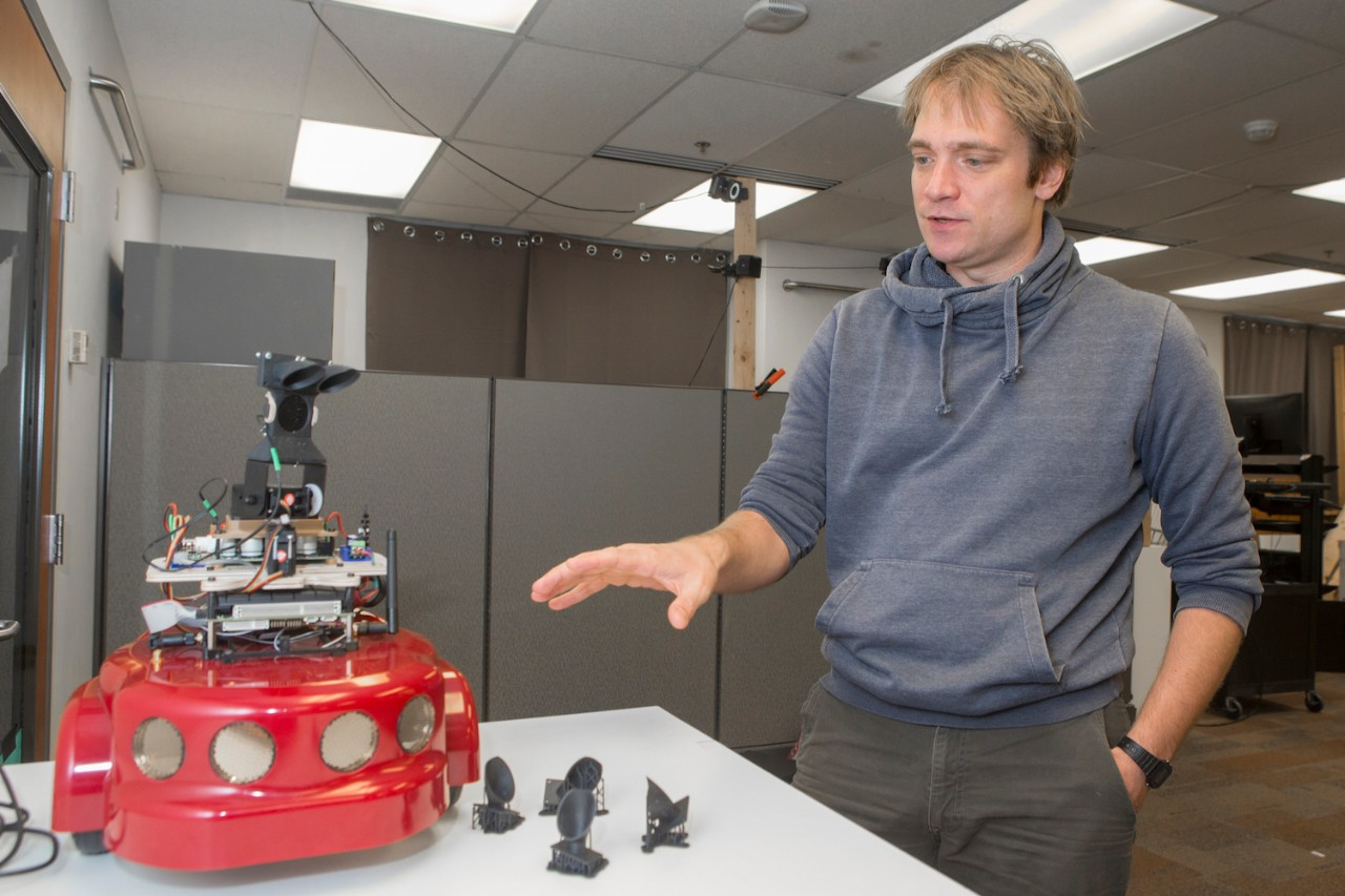 Dieter Vanderelst stands next to a table with a small wheeled robot studded with speakers and acoustic sensors.