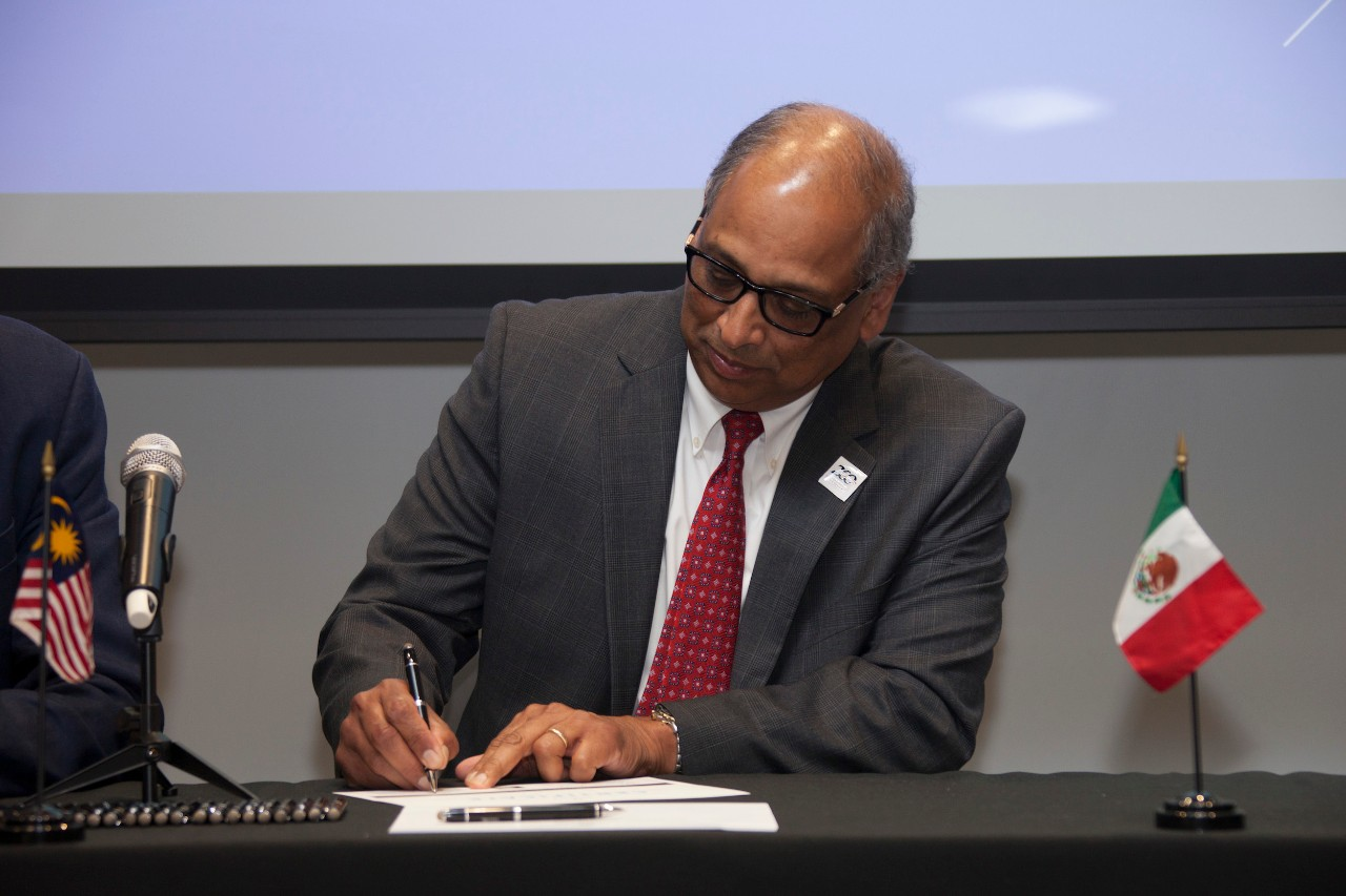 a man seated at a table signing a paper