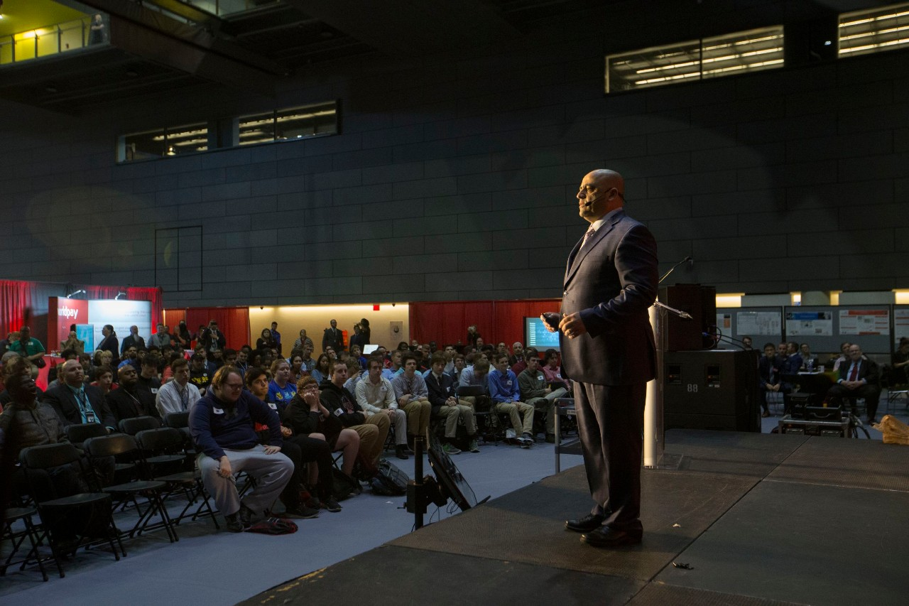 A man standing on a stage speaking before an audience