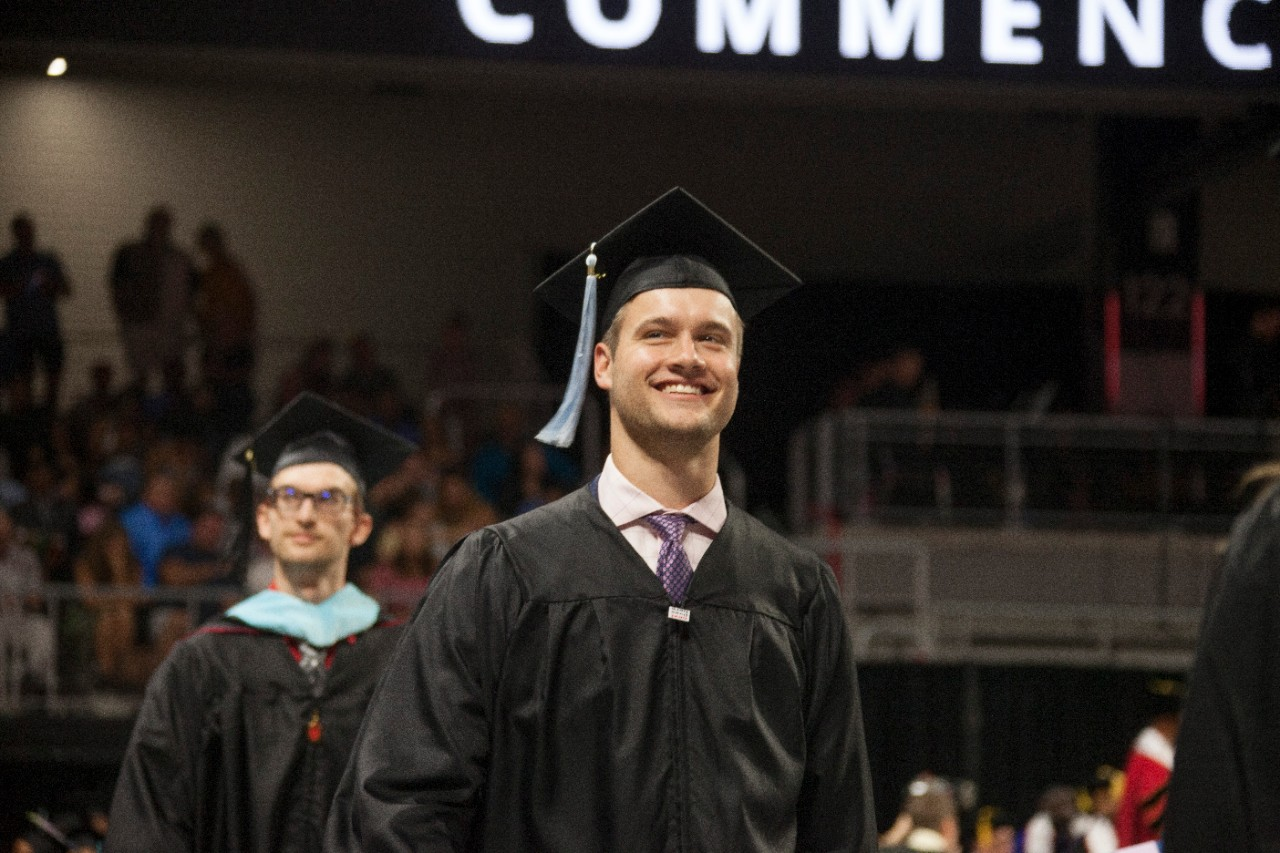 A student smiles in his cap and gown.