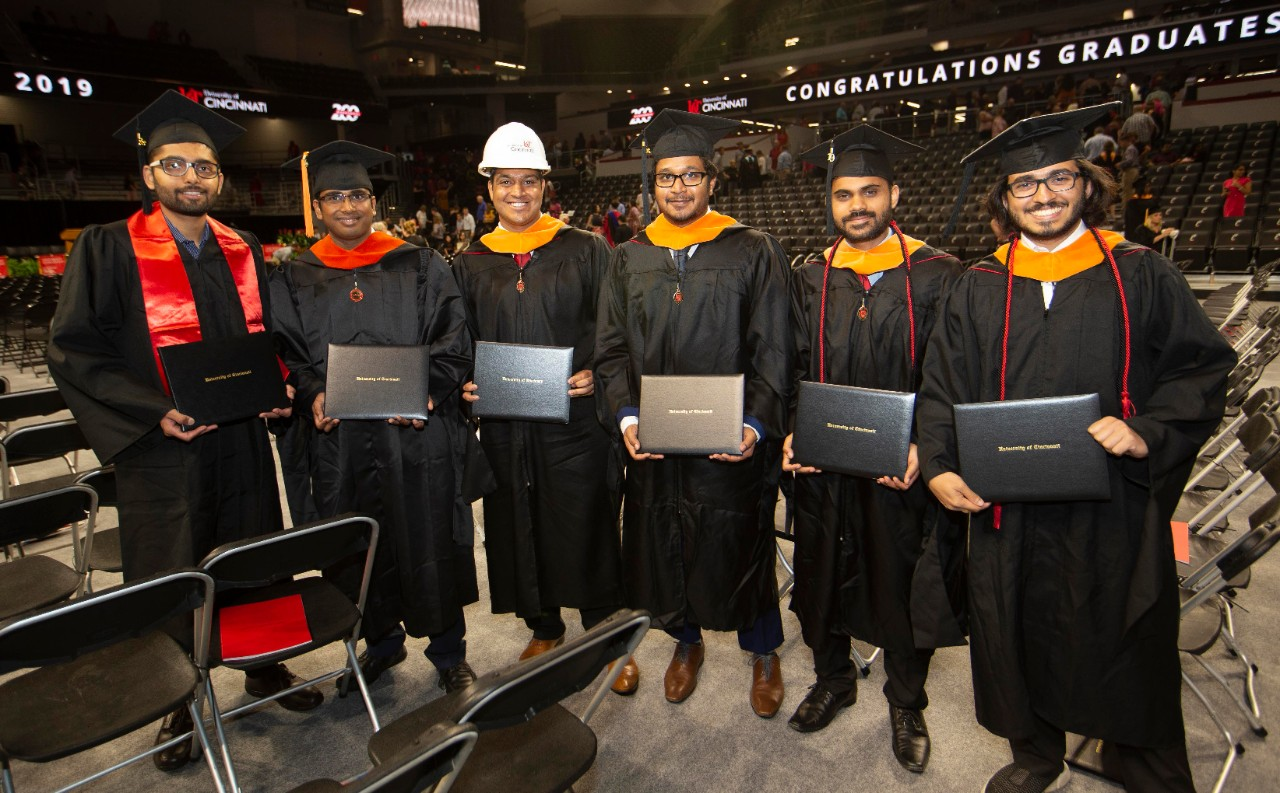 Engineering students, one wearing a hard hat, hold up their diplomas at Fifth Third Arena.