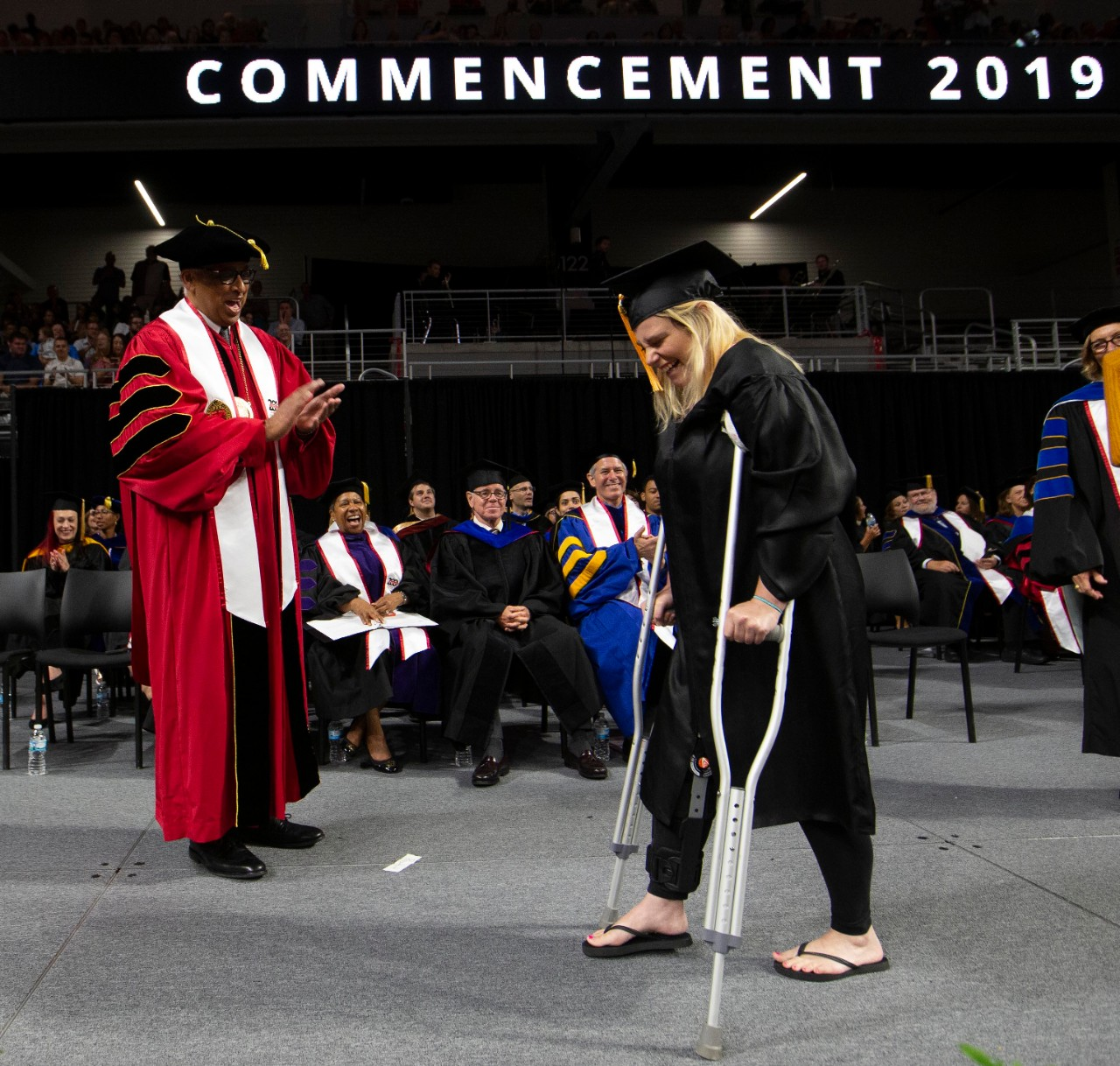 A student on crutches walks on stage to shake President Neville Pinto's hand.
