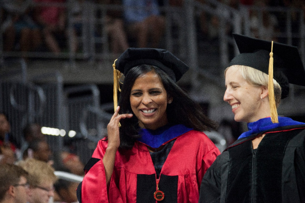 Students smile in their caps and gowns.