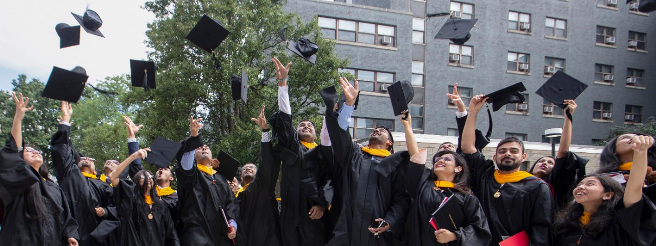 UC engineering students toss their mortar boards in the air after UC's commencement.