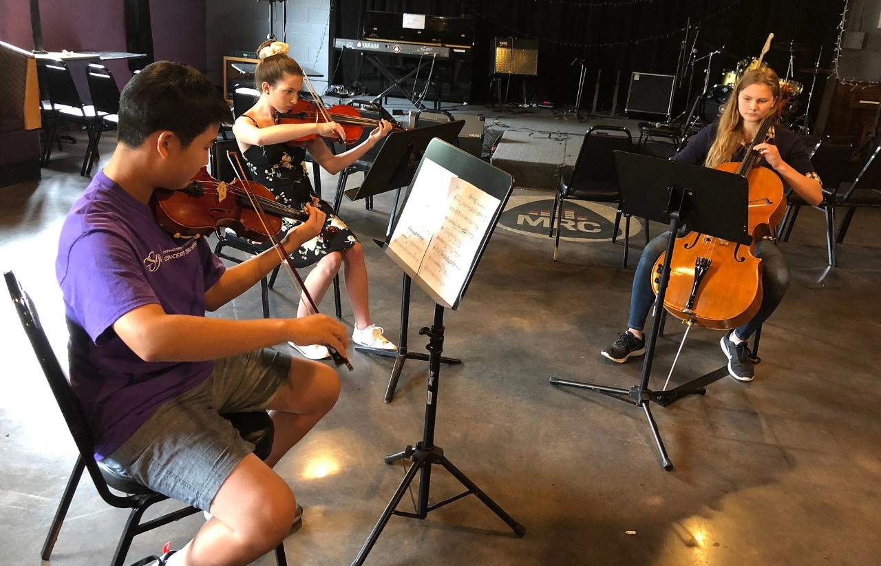 Young musicians rehearsing classical music instruments in a school music room.